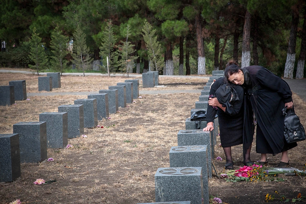Irina Calishvili (right), who lost her only son Aleksandre in the airplane crash, comforts a family member of a fallen soldier.