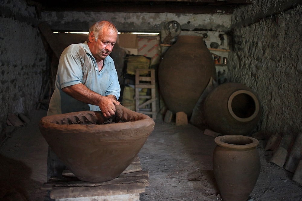 Remi Kbilashvili adds clay to a terra cotta vessel, which will be used to make Georgian kvevri wine.