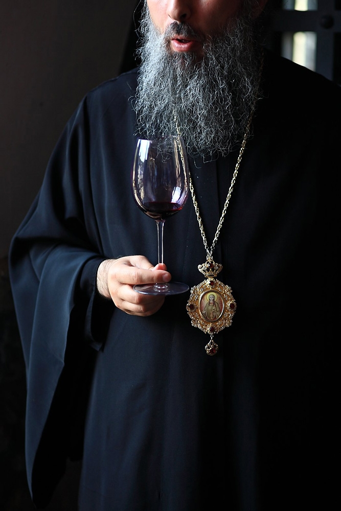 A monk at the Alaverdi monastery shows symposium participants one of the wines they produce.