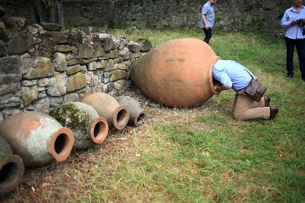 A participant with the wine symposium sticks his head in an old kvevri clay vessel at the Ikalto wine academy.