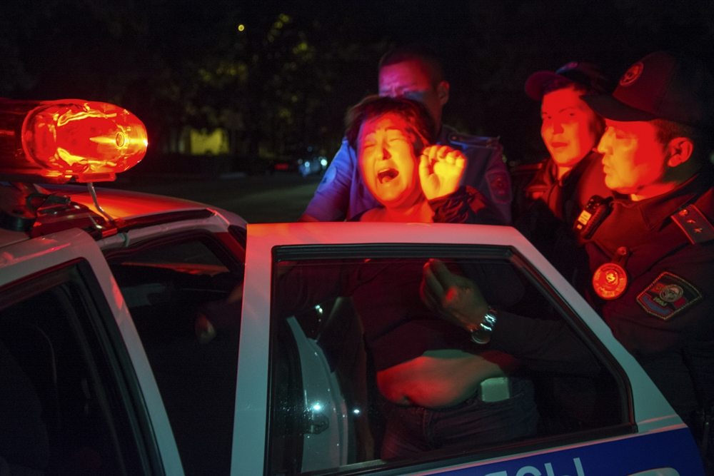 Police officers in Bishkek drag an argumentative, inebriated woman into a waiting police car.