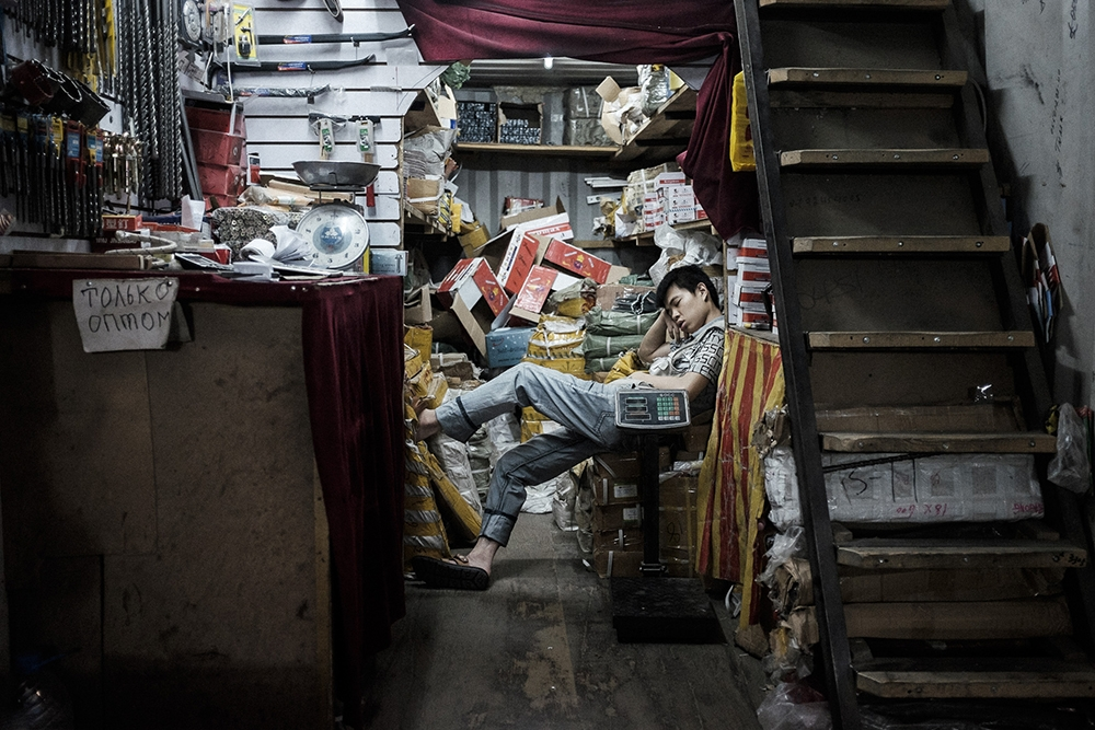 A young trader naps in the Junghai market, which is a part of the Dordoi complex.