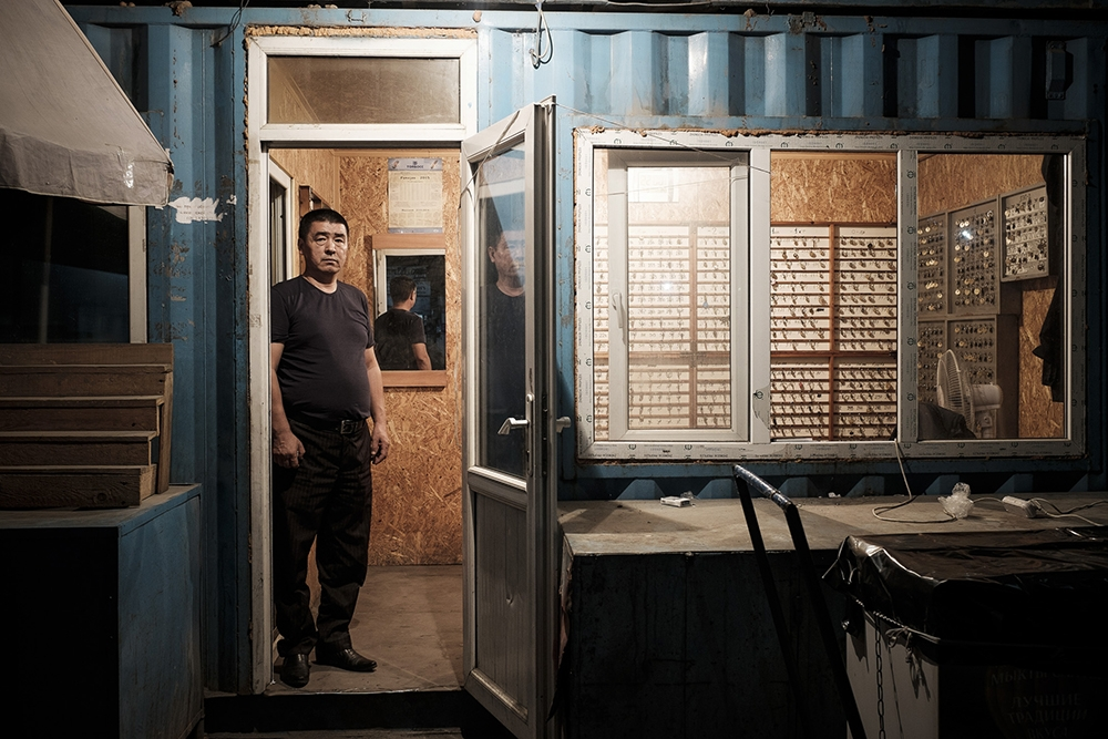 Meder, the 52-year-old head of security at the bazaar, stands at the door of the main security office during his night shift.