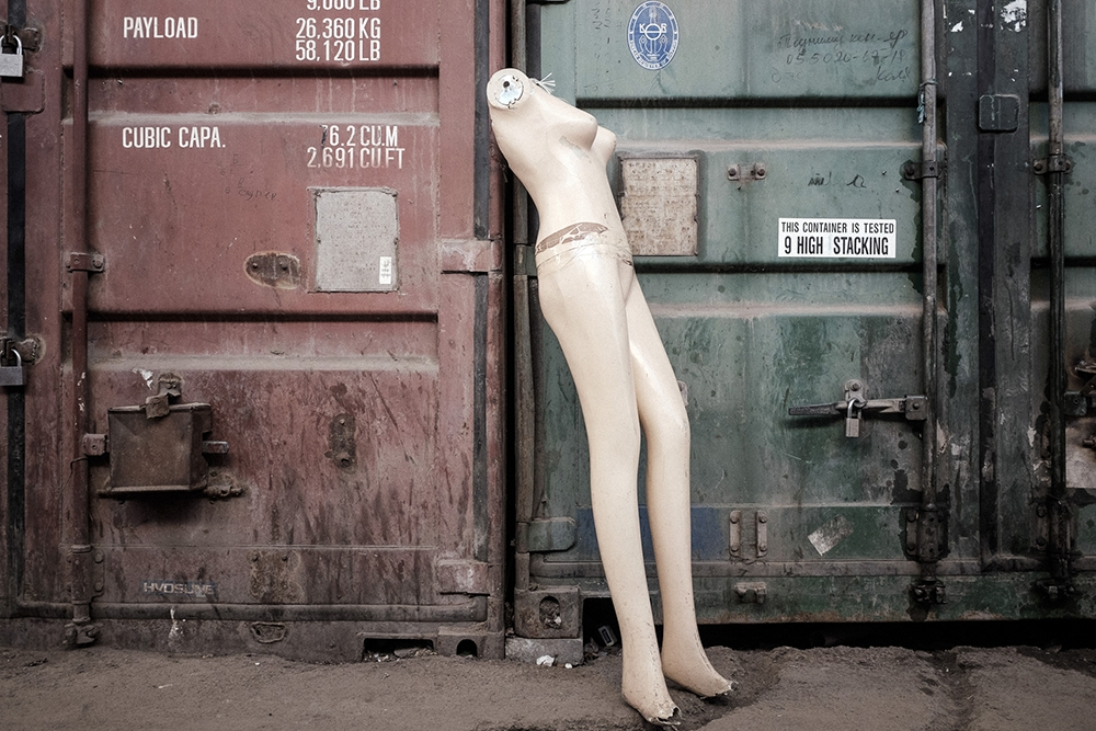A nude mannequin leans against one of the thousands of containers in the bazaar.