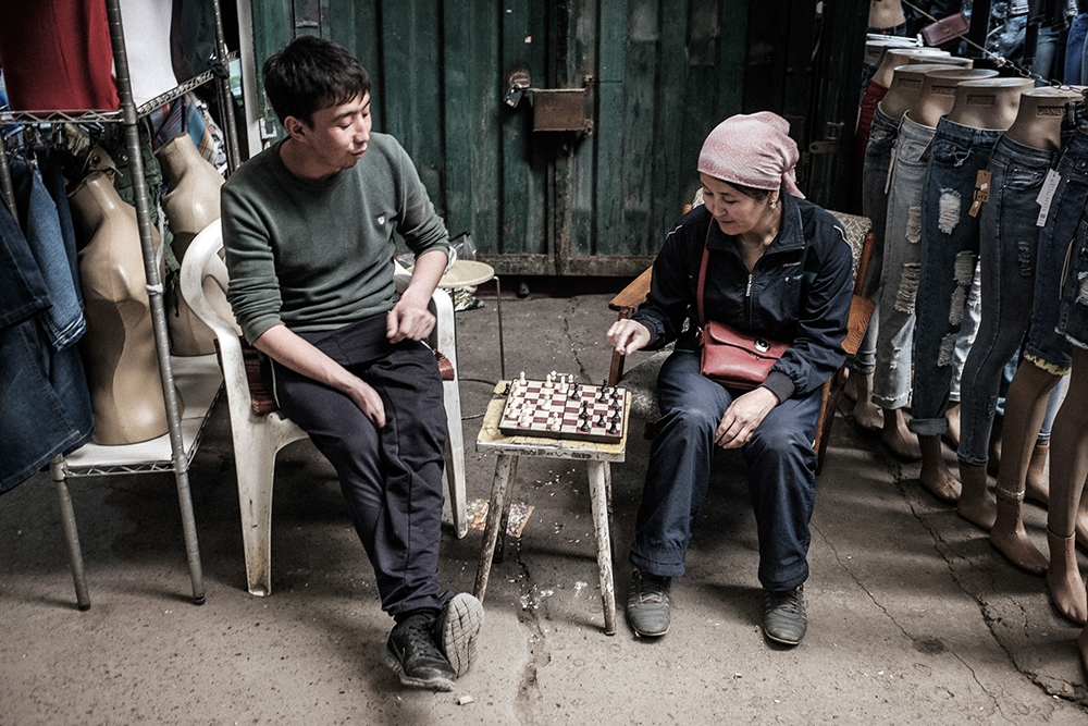 Traders play chess during a break, when customers and shop owners are busy eating lunch.