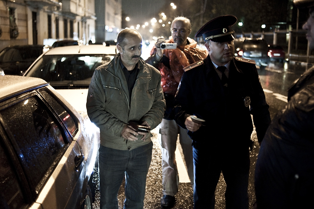 Police detain an unlicensed taxi driver from Azerbaijan during a sting to nab unregistered migrants.