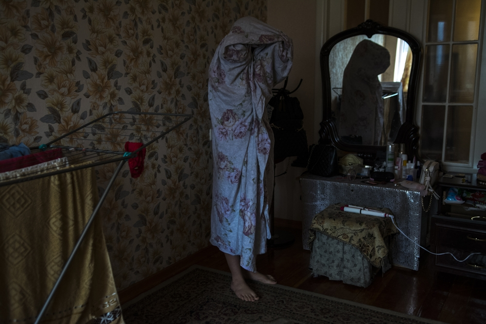 A sex worker in Bishkek covers herself up with a sheet during a police raid.