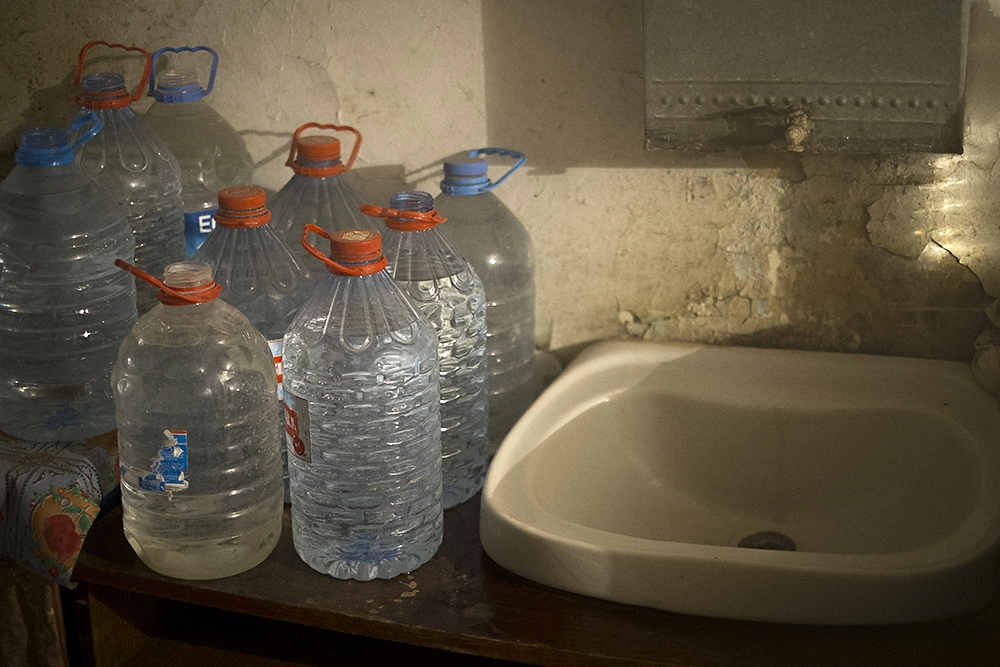 With no indoor potable water source, dorm residents collect water outside in plastic bottles to be used for daily needs.