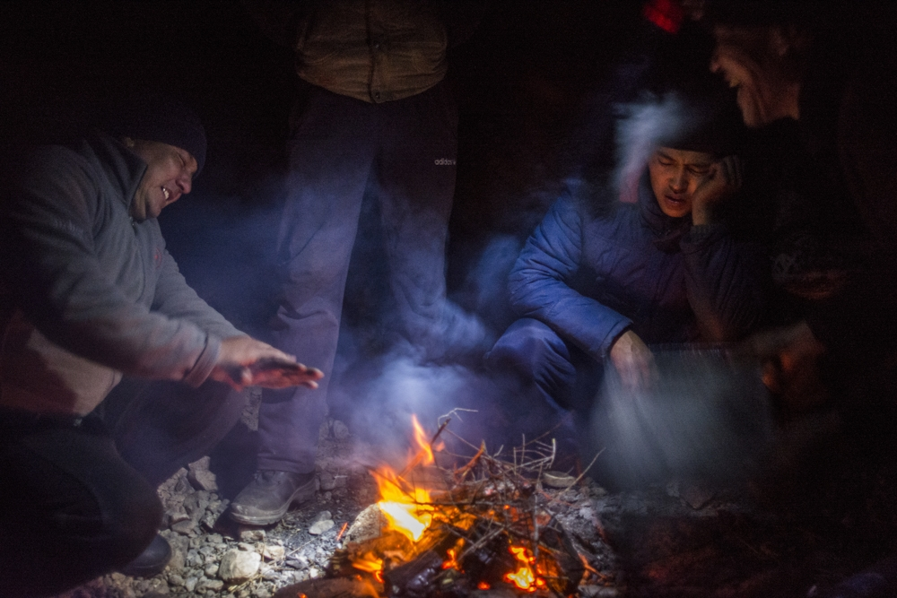 Truck drivers in the mountainous city of Naryn warm themselves up by the fire as they await their next assignment.