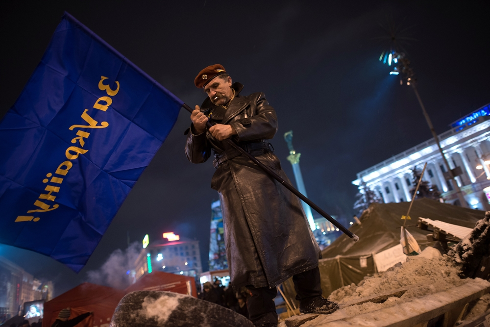 "A veteran places a flag imprinted with ""For Ukraine""  on a newly built barricade in Maidan Square."