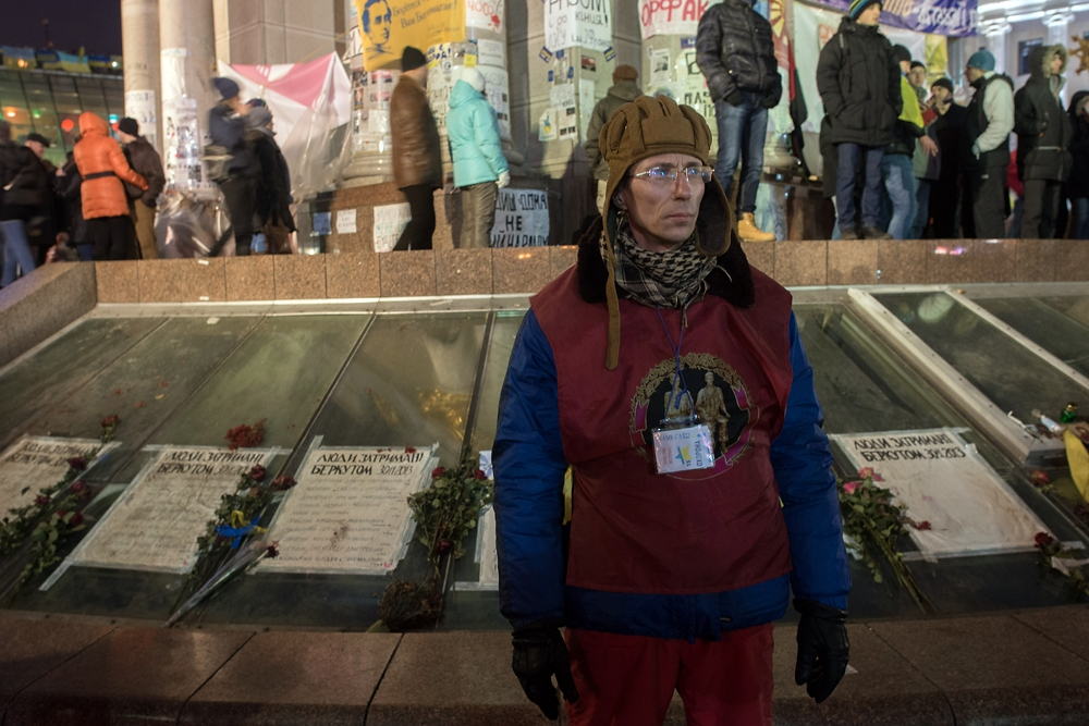 A Soviet army vet stands in front of a memorial for people were injured on Nov. 30 by riot police.
