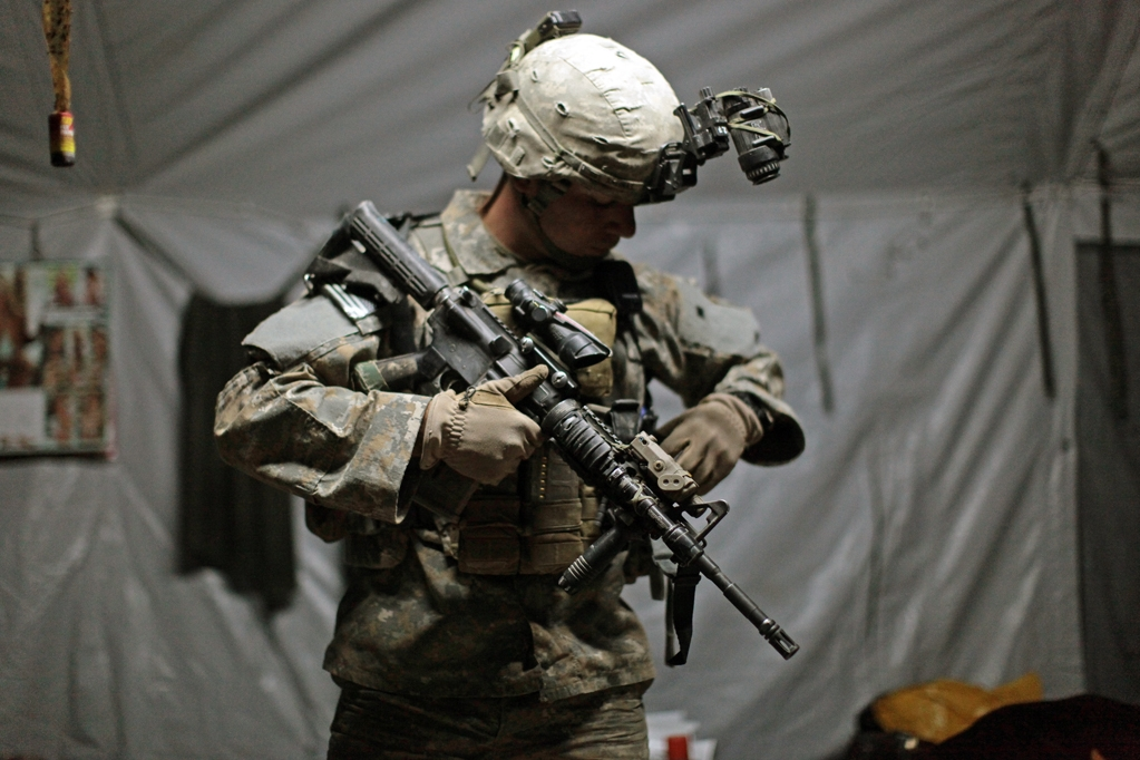 A US soldier with the 82nd Airborne's B Company checks his weapon and spare ammunition ahead of a night raid.
