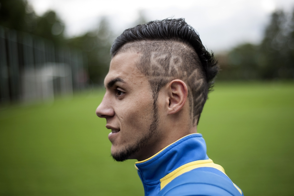 A football player has his team's name shaved in his hair at a Moscow tournament for Tajik labor migrants. (Konstantin Salomatin)
