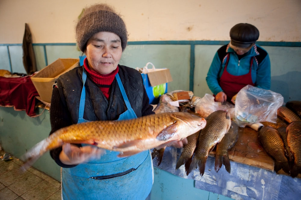 A woman displays the catch of the day in a fish shop in the town of Aral.