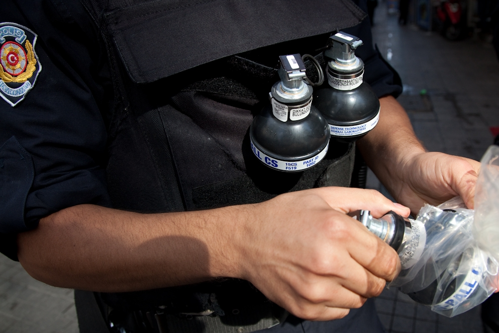 A Turkish policeman brandishes tear gas grenades in preparation for the expected clashes with protestors in Istanbul.