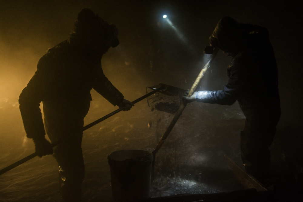 Men sift through ash to find fragments of unburnt coal dumped from a thermal power plant in Bishkek.