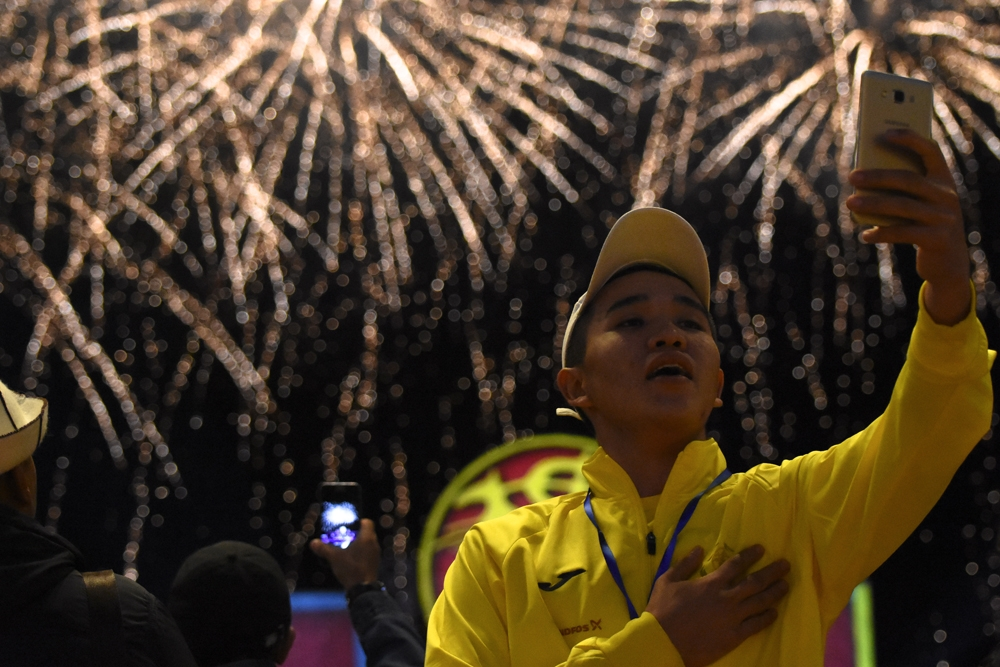 A volunteer taking a selfie during the fireworks finale that accompanied the national anthem at the end of the opening ceremony.