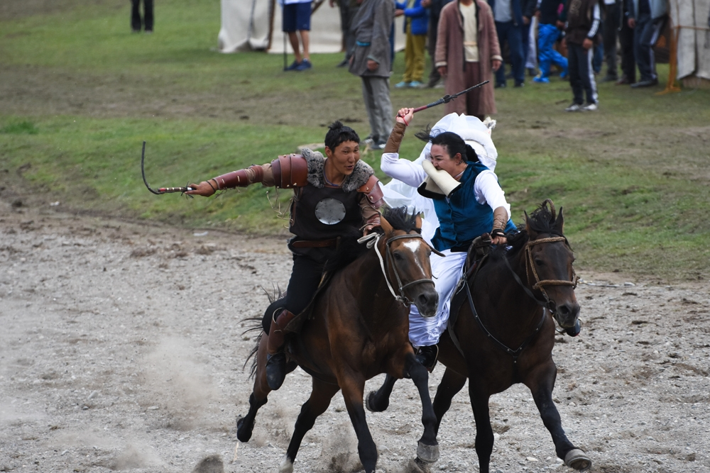 Actors demonstrating the game of Kyz-kumay, where a rider who fails to kiss a girl mid-gallop is whipped on the way back.