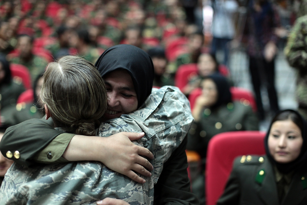 An American trainer and her graduating charge hug before the ceremony begins at the Afghan National Military Academy.
