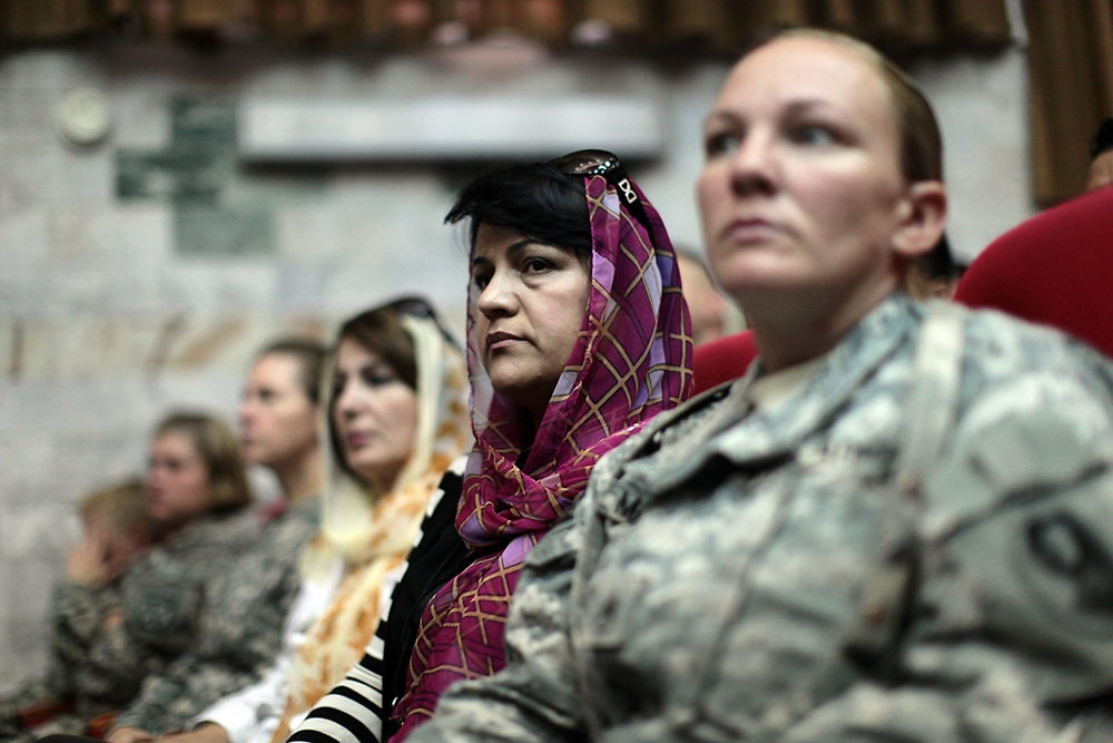 Dressed in the Muslim attire typical of liberal urban Iranian women, Afghan translators for the US military watch the event.