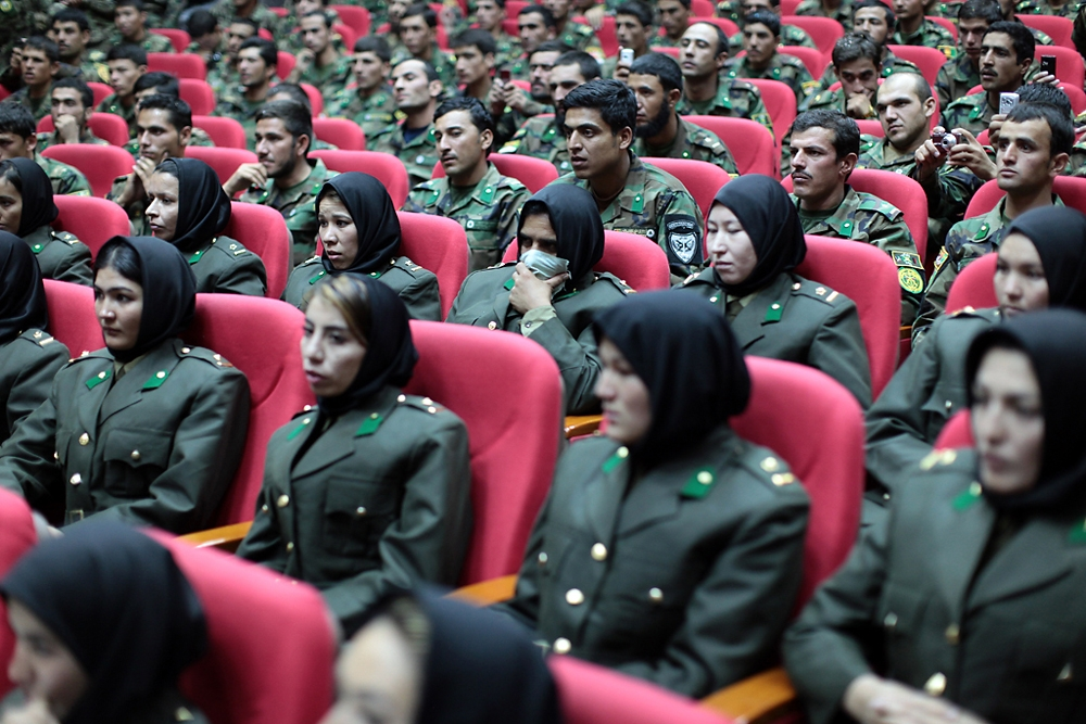 An officer, masking her face from an infection, sits in the ranks of female graduates watching the ceremony.