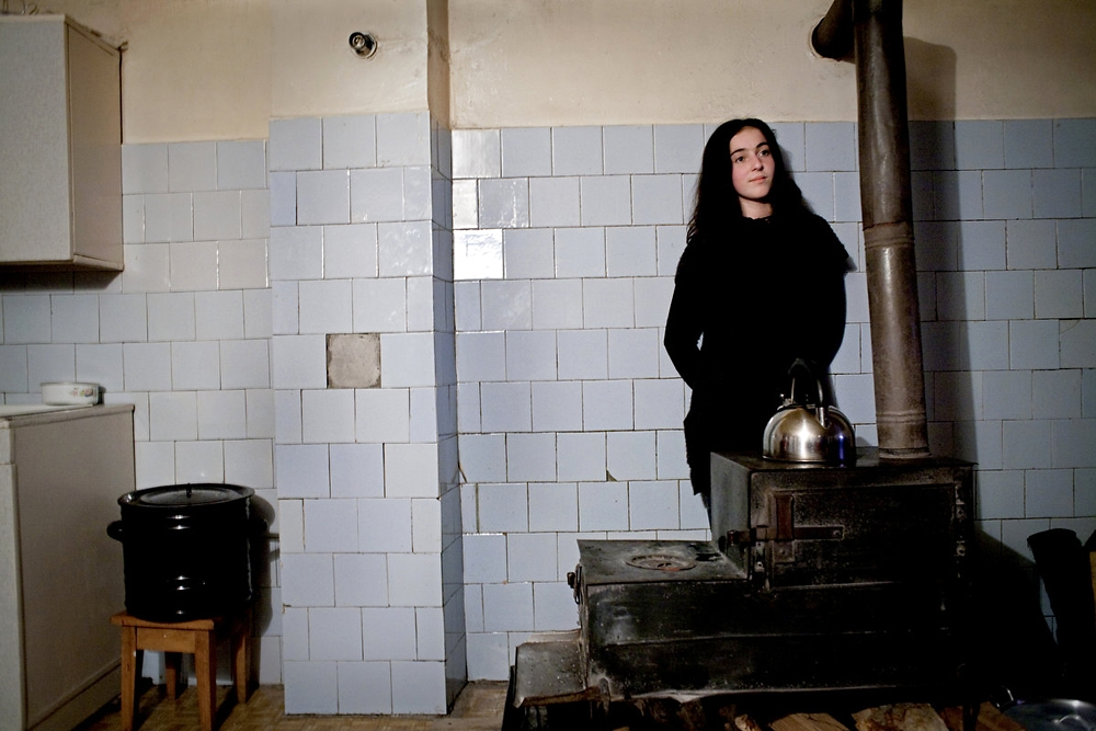 Markha, the 15-year-old daughter of Shorena Khangushvili, stands by the wooden stove used to heat her family's kitchen.