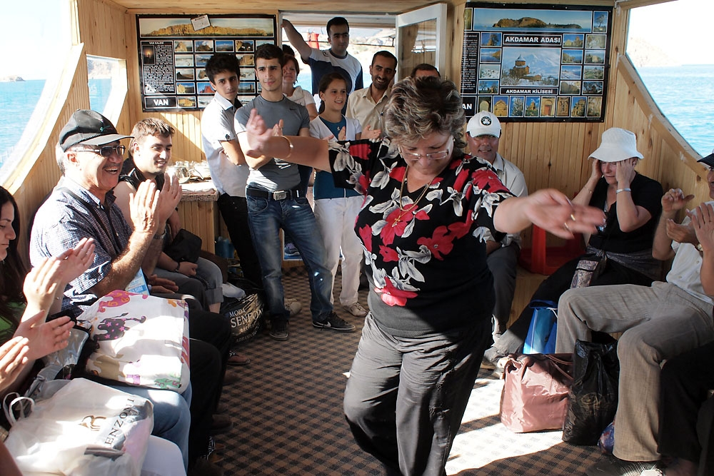 An Armenian woman, part of a group that came to the service from Armenia, dances a folk dance on the boat back to the mainland.