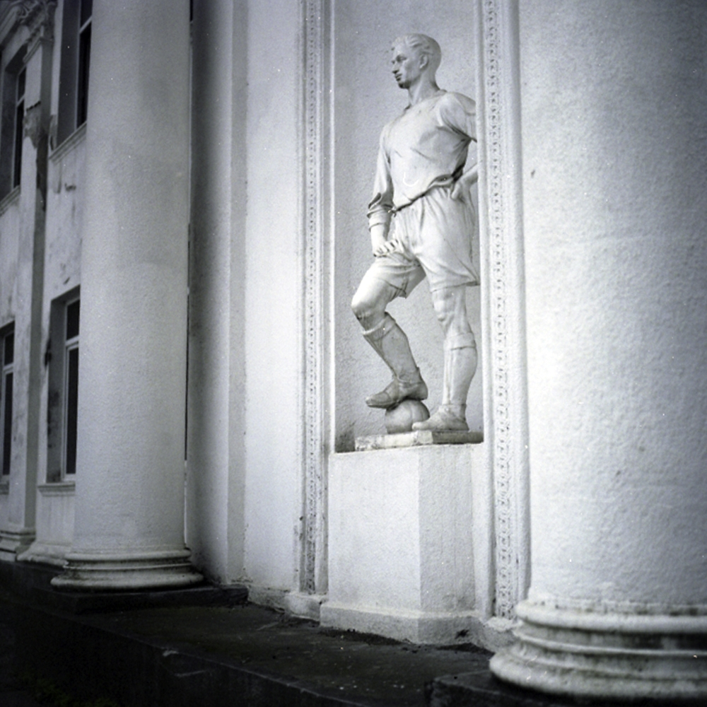An all-white neo-classical building at a main intersection leading into the center of Sukhumi features statues of athletes.