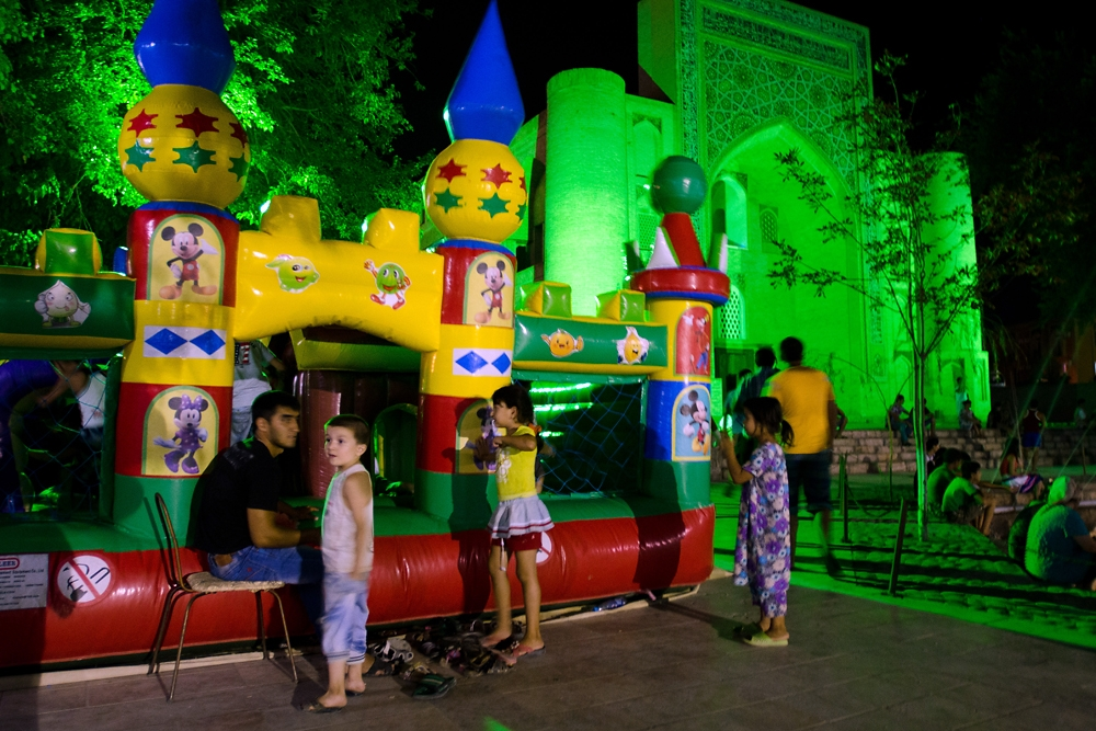 Children play in an inflatable bounce playground during the evening in the Lyabi Khauz square of Bukhara.