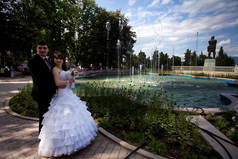 Newlyweds pose on their wedding day in a park in Stepanakert.