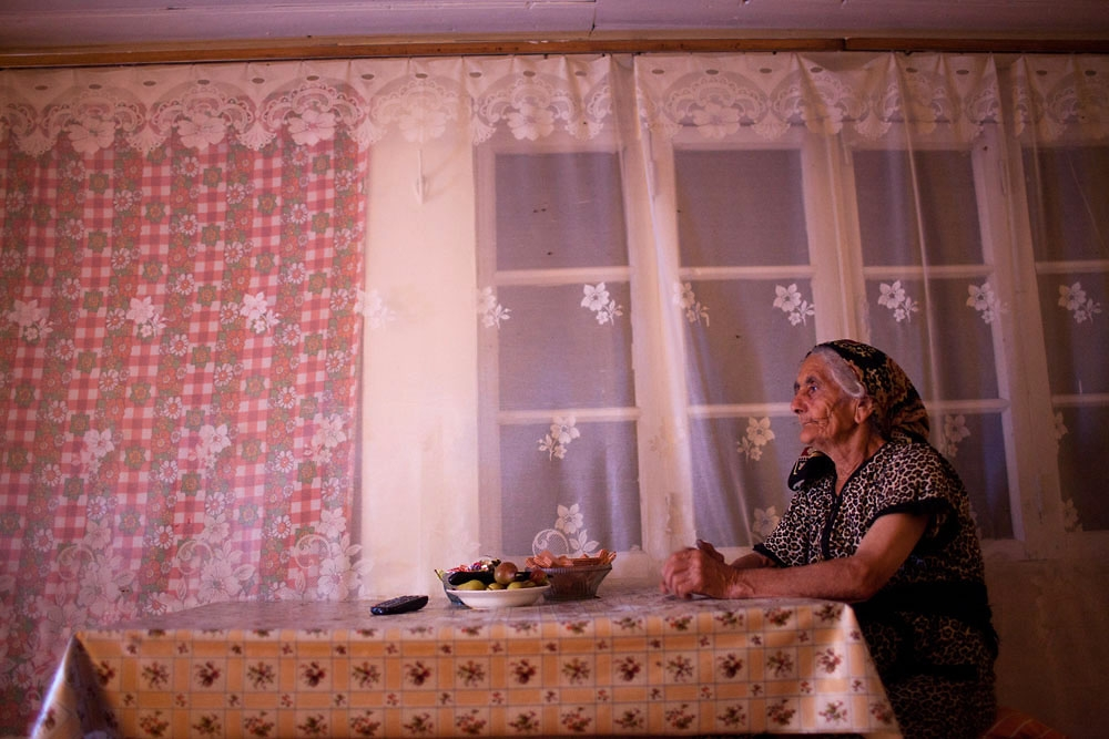 Arega Martirosyan, from the village of Pletants, watches television news after polling stations closed on July 19, 2012.