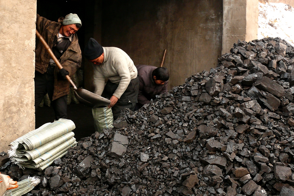 Men shovel raw coal into bags which they sell at a wholesale price of $.72 a bag to re-sellers.