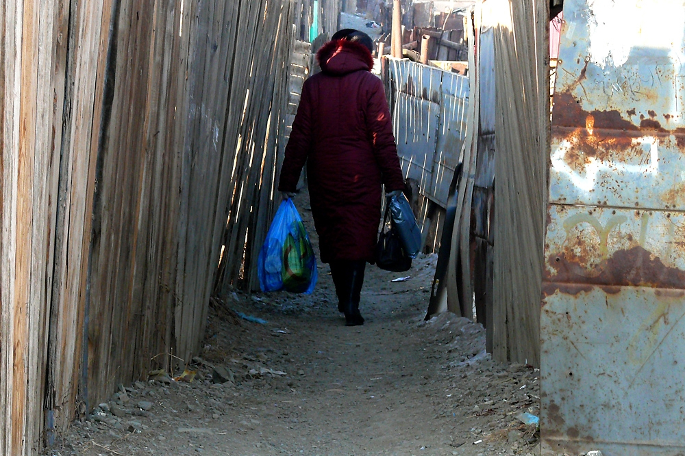 A woman carrying groceries picks her way through the narrow maze formed by neighborhood fences called 'hasha.'