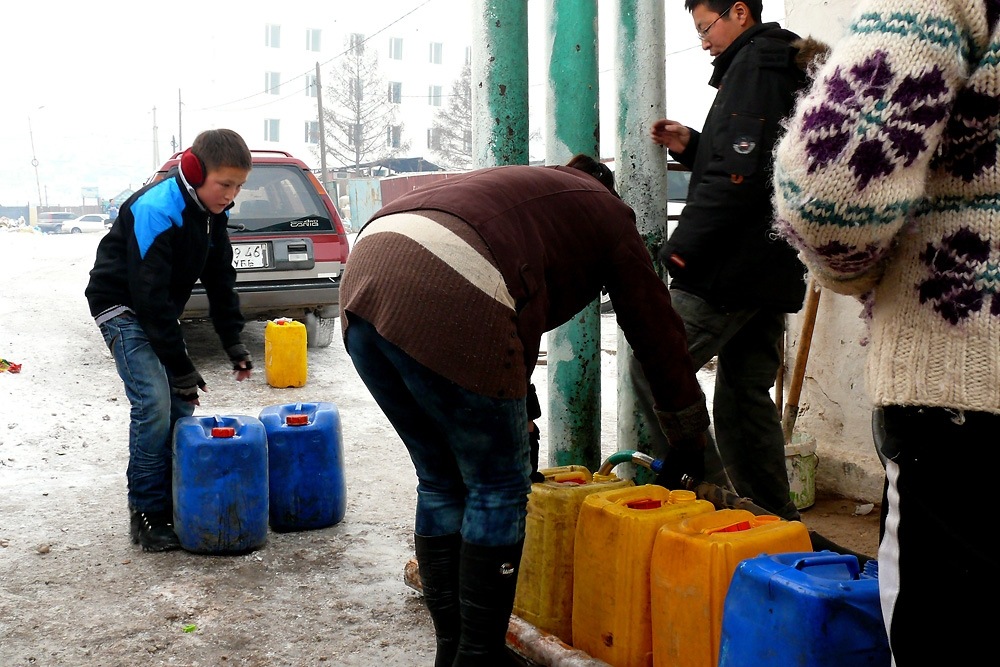 Collecting water at the nearest water kiosk in the freezing cold is a daily inescapable chore of ger district residents.