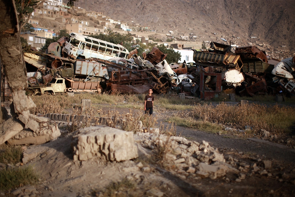 A Jangalak resident wanders through the rubble and junked vehicles littering the neighborhood.