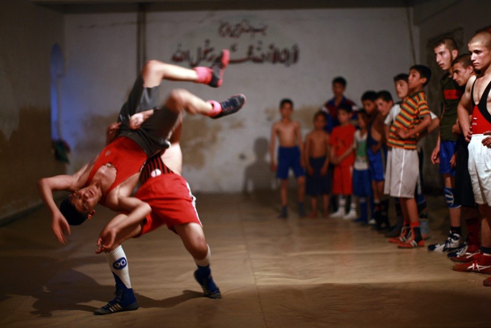 A young wrestler throws his opponent to the ground during a training session at a gym inside Jangalak.