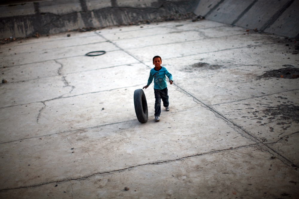 A boy rolls a tire along the bottom of an empty reservoir.