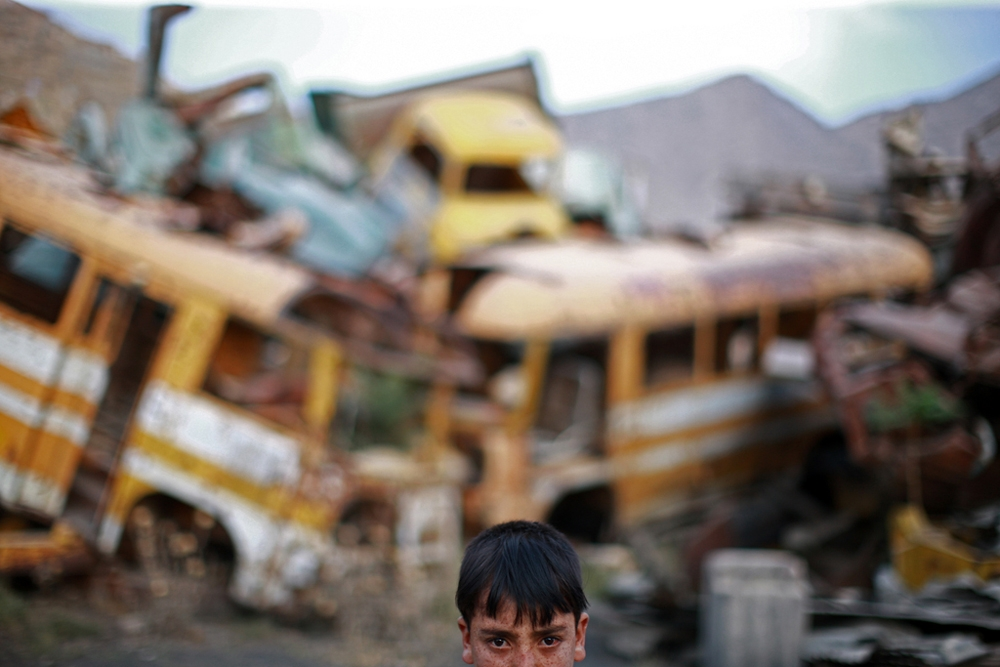 A refugee boy plays in a yard full of trashed vehicles.