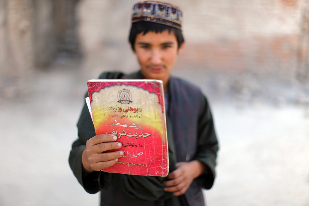 "A boy holds up a Dari-language version of the ""Holy Traditions of the Muslim Prophet"" school book."