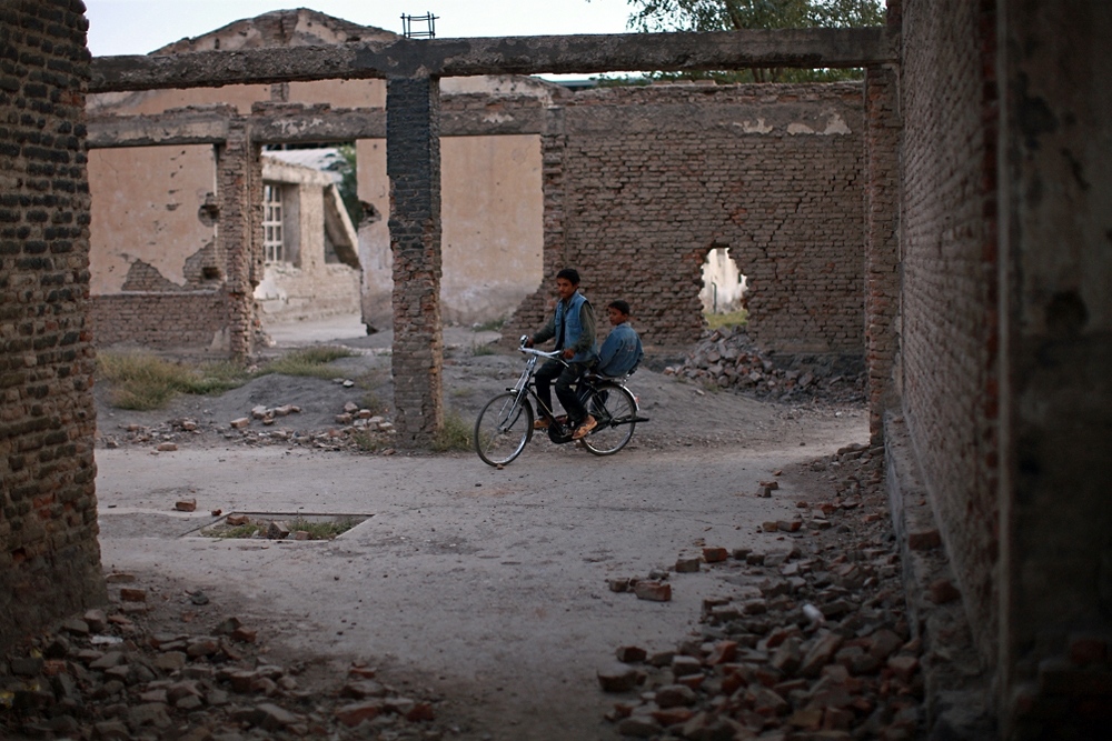 Two boys ride an antique bike around the rubble of Jangalak.