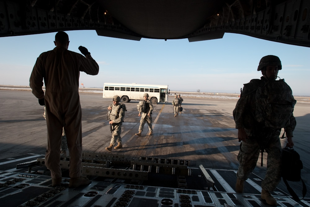 A payload master directs soldiers deploying to Afghanistan to their seats on board a C-17. (Photo: David Trilling)