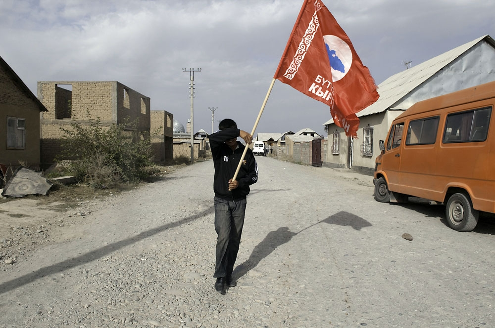 A boy carrying a political party flag shields his eyes from the blowing dust.