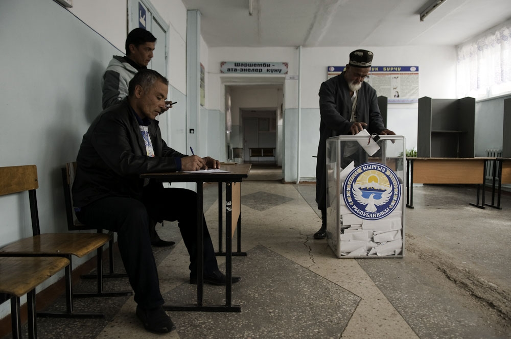 An ethnic Uzbek man drops in his vote at a polling station in the village of VLKSM near Osh.