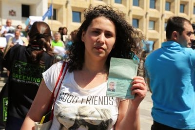 Azerbaijani journalist Lelya Mustafayeva shows the passport of her husband, reporter Afgan Mukhtarli, now in a Baku jail.