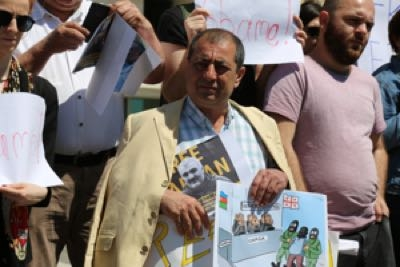 A Tbilisi protester carries a photo of reporter Afgan Mukhtarli and a cartoon that blames Georgia for his disappearance.